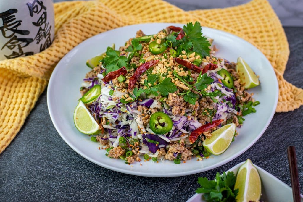 Keto Thai egg roll bowl garnished with chopped peanuts and lime