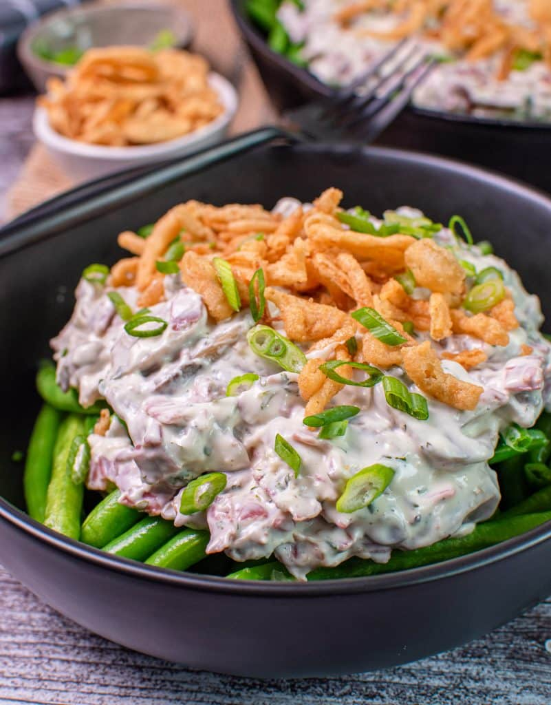 bowl of green been casserole topped with cream chipped beef and crispy onions