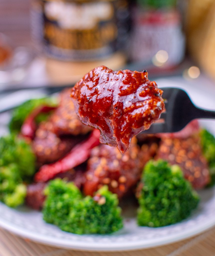 Single piece of low carb general tso chicken on a fork