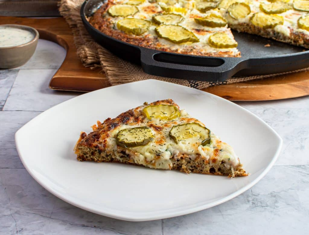 Single slice of dill pickle pizza on a plate