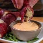 dipping pastrami roll ups into Russian dressing