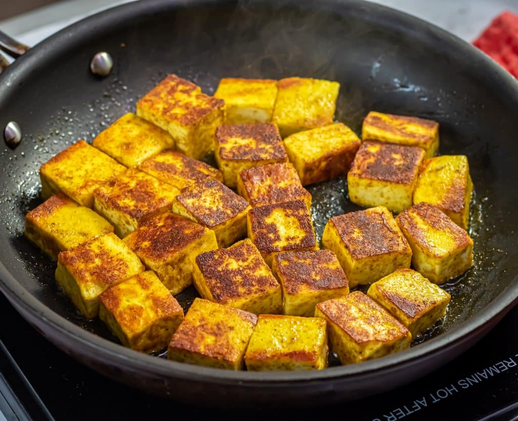 paneer cheese with curry powder sautéed in a nonstick pan