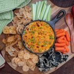 overhead view of crab dip with pork rinds, carrots, celery and crustinis