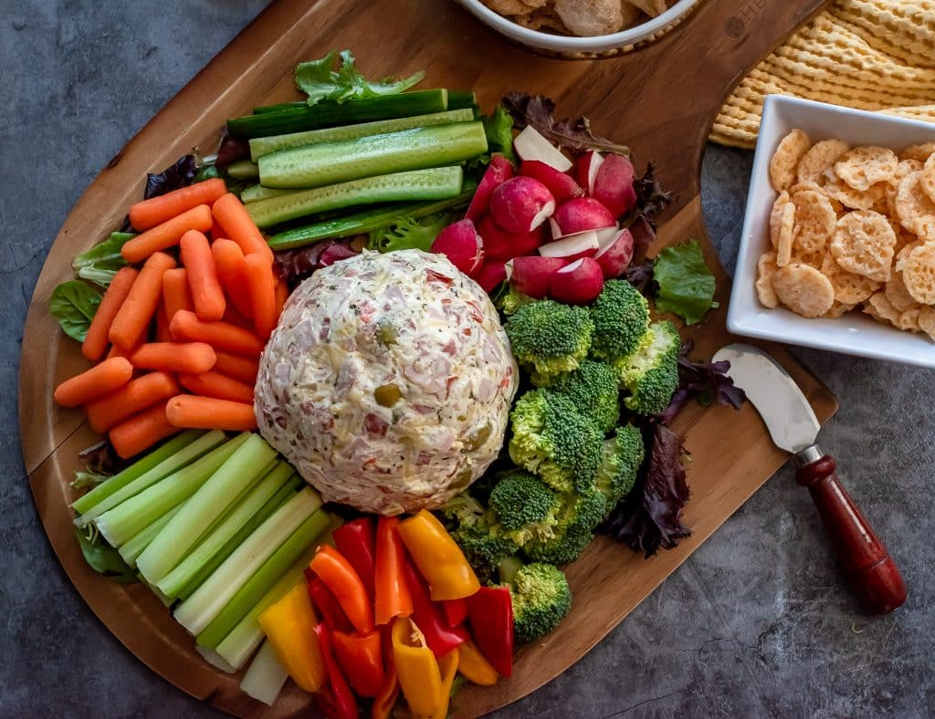 Muffuletta dip served on a pizza peel with veggies and pork rinds