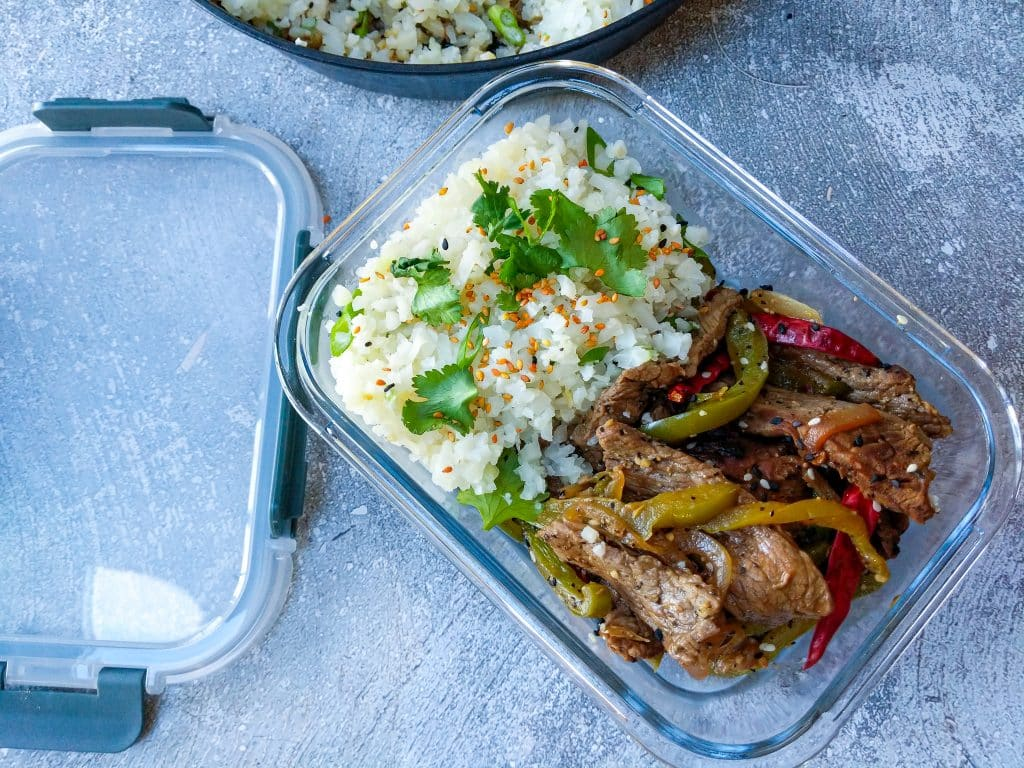 keto peppersteak portioned into glass meal prep container