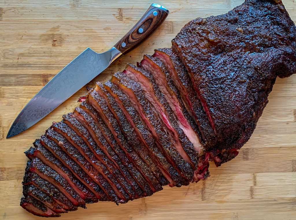 Sliced Texas brisket on wood cutting board with chef knife