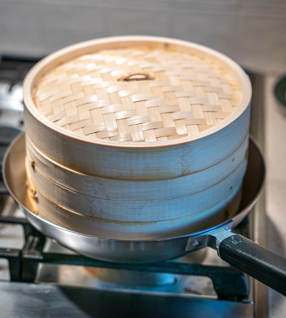 bamboo steamer on top of a carbon steel wok