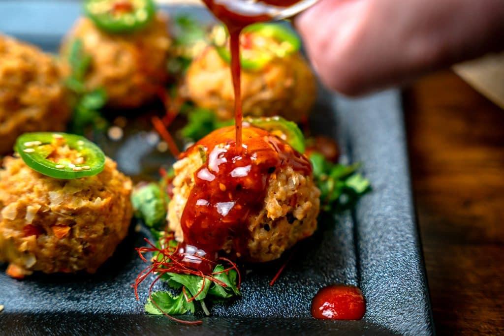 pouring dumpling sauce over chicken meatball