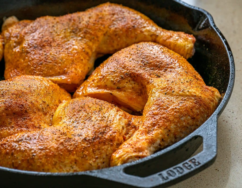 uncooked chicken leg quarters in a cast iron skillet with lemon pepper seasoning
