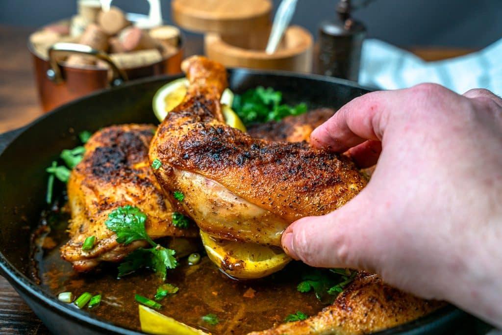 chicken leg quarter in a cast iron skillet with lemon pepper seasoning