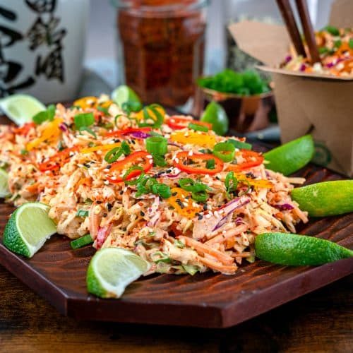 kimchi coleslaw garnished with sesame seeds, chili flakes and lime wedges