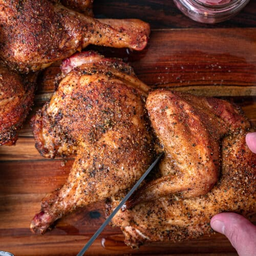 cutting a smoked half chicken into quarters with a chef knife