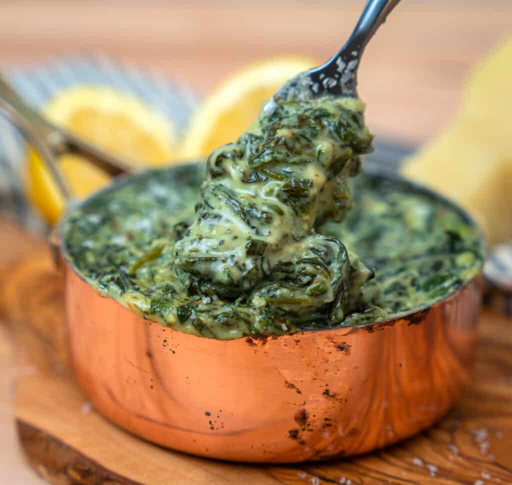 using a fork to serve keto creamed spinach out of a copper pan